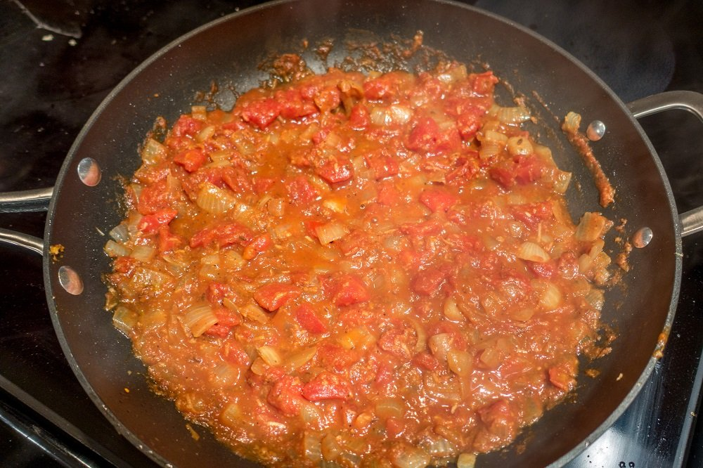 Add the tomatoes and spices to make the curry for the aloo gobi