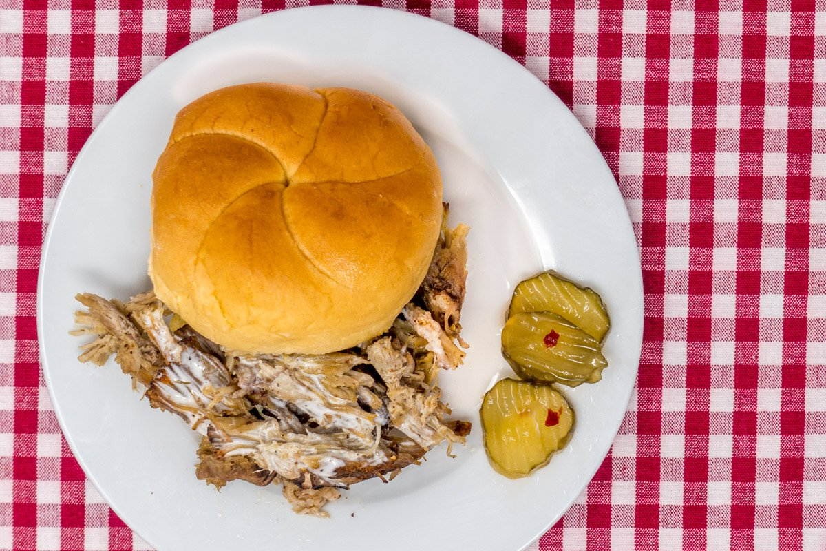 Pulled pork sandwich served with the best white BBQ sauce recipe and fire and ice pickles