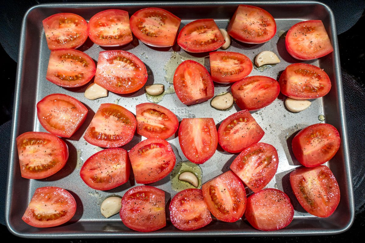 Plum tomatoes and garlic on baking sheet for tomato basil soup