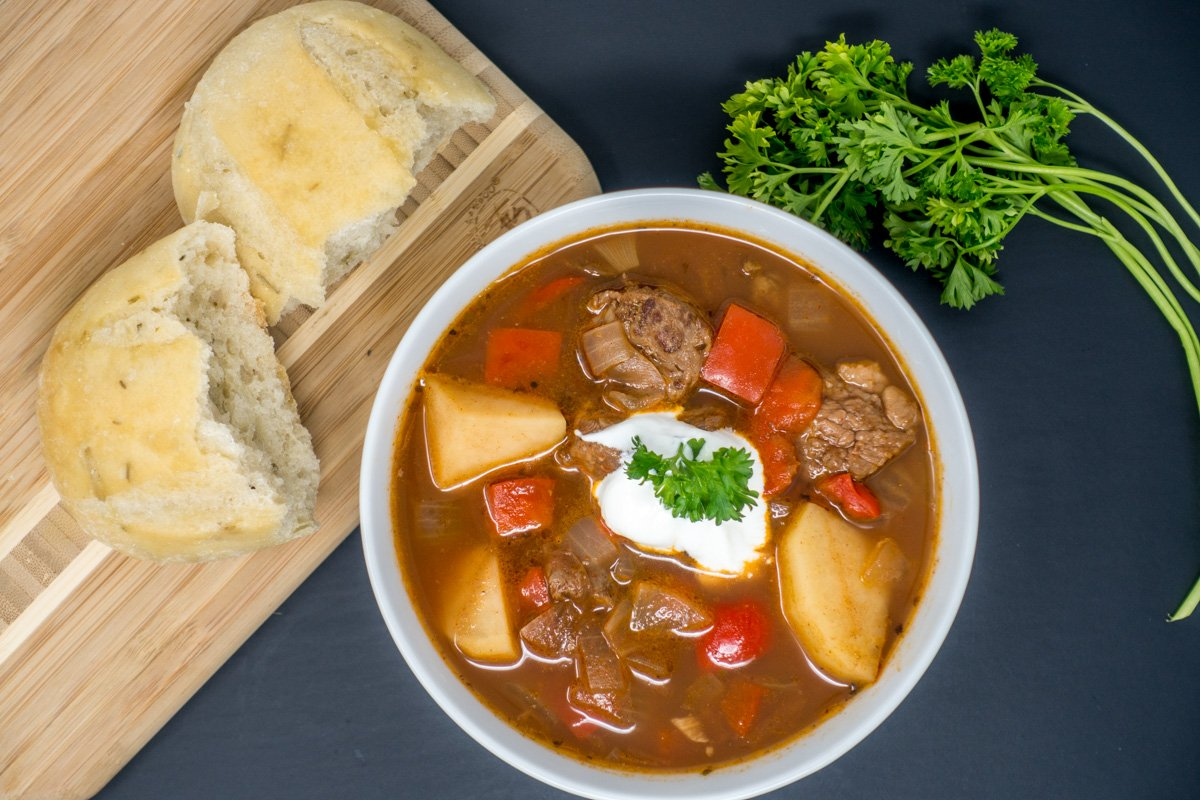 Finished German goulash in a bowl, topped with sour cream and served with crusty bread