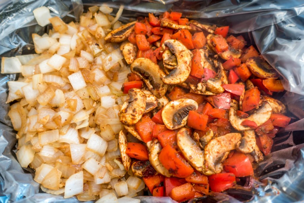 Cooked onions, mushrooms, and peppers in the slow cooker
