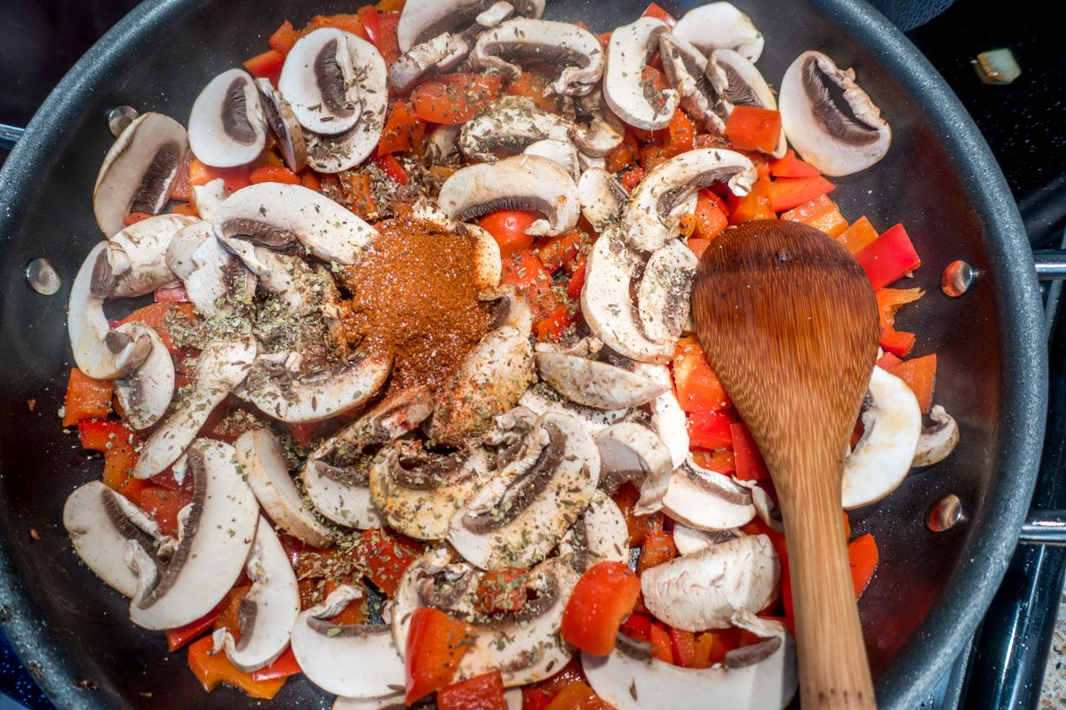 Red bell pepper, sliced mushrooms, and spices in a pan