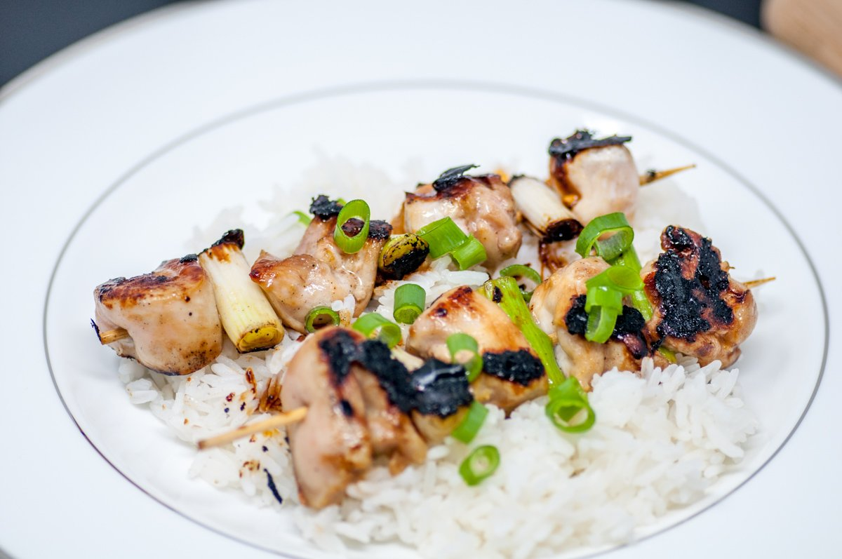Chicken yakitori skewers over rice garnished with green onions