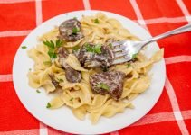 Slow cooker beef stroganoff with noodles on a plate with fork