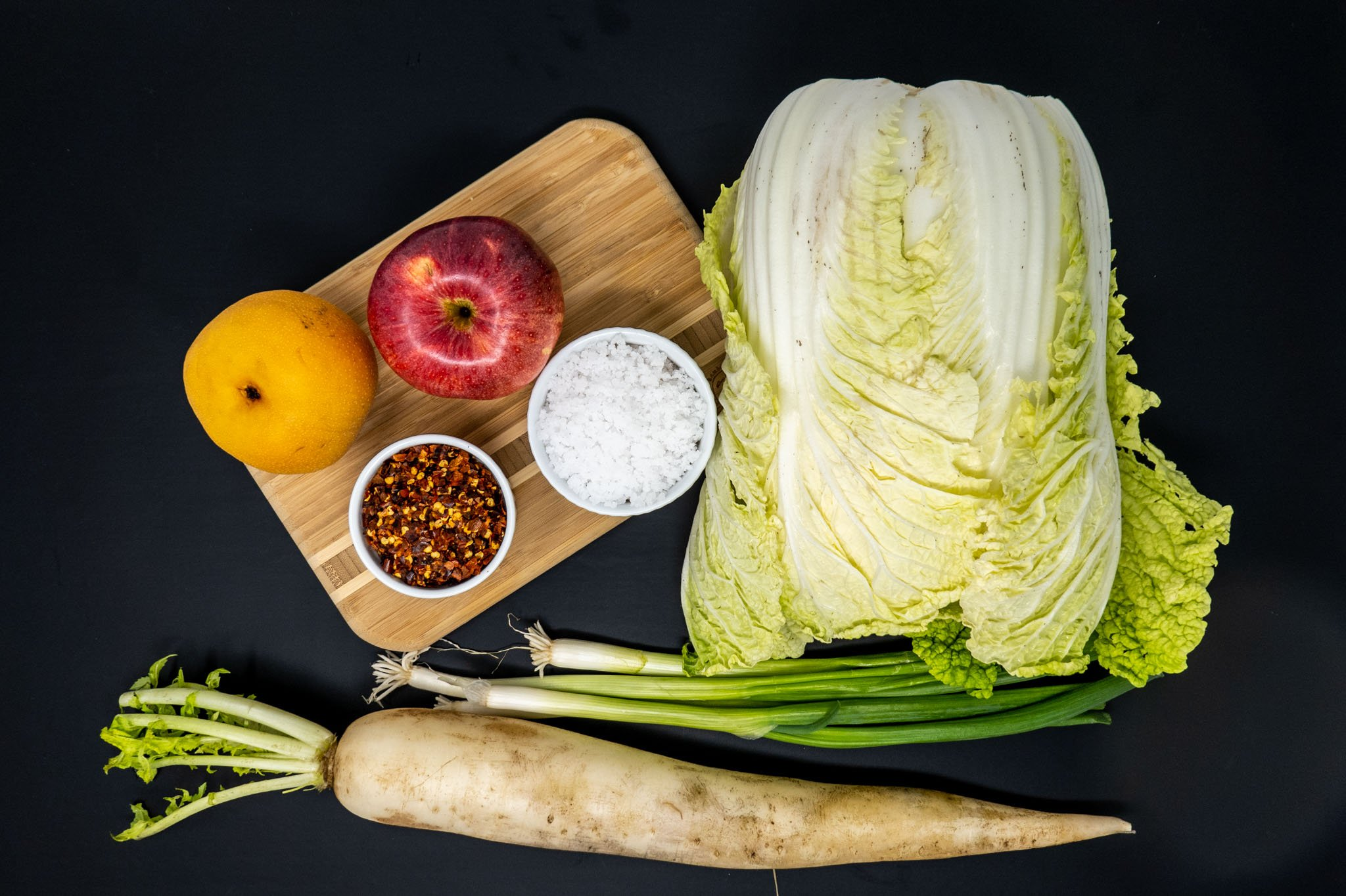 Cabbage, daikon radish, Asian pear, and other ingredients for the Korean kimchee recipe on the table