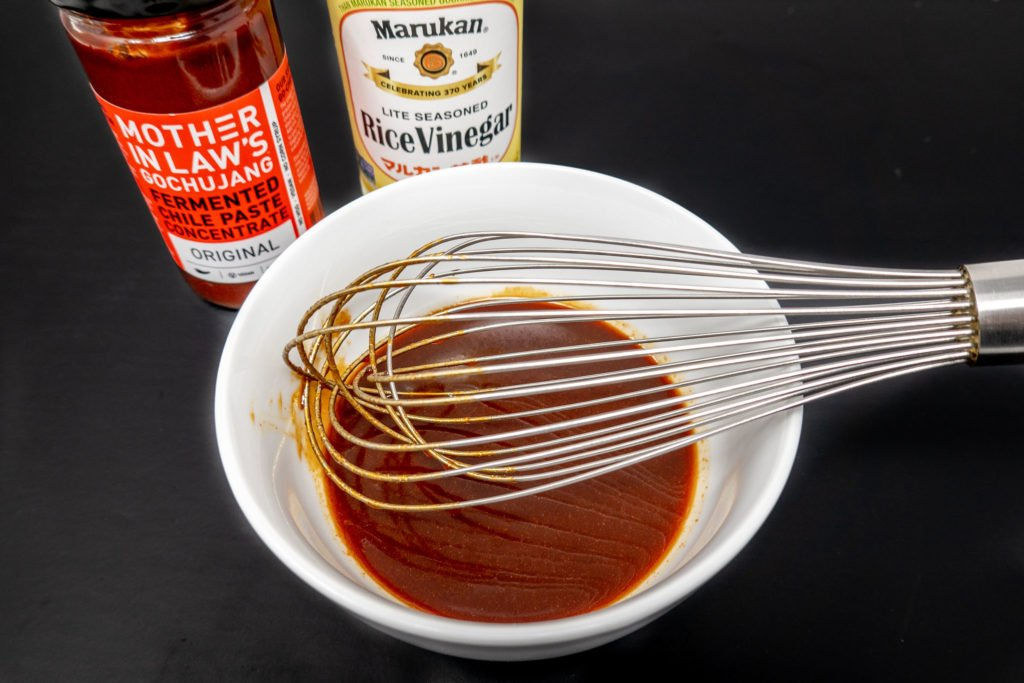Gochujang and rice vinegar bottles with whisked BBQ sauce in bowl
