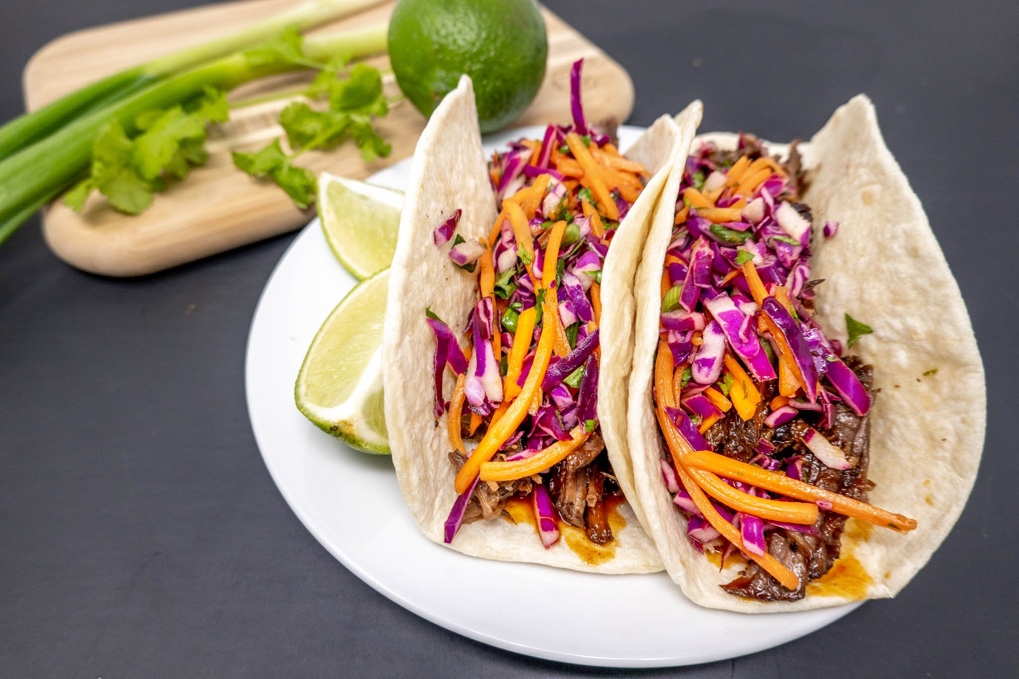 Tacos on a plate with limes and scallions