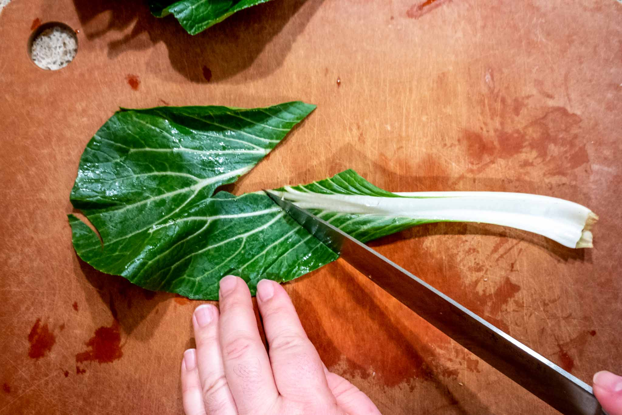 Person removing  bok choy stem from leaf with a knife