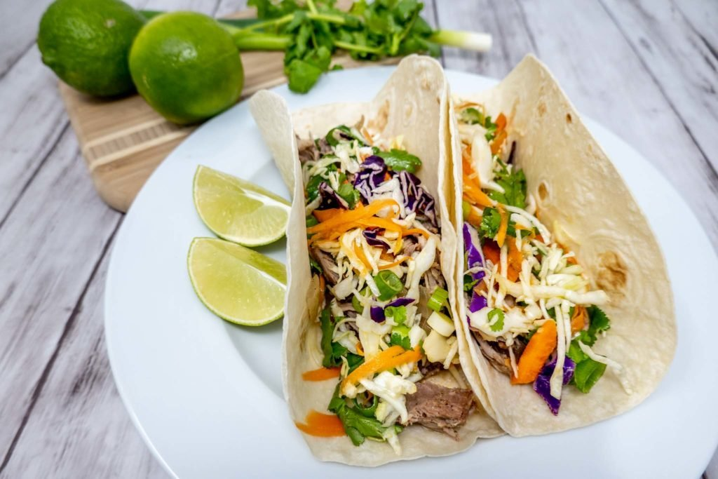 Tacos and slices of lime on a plate