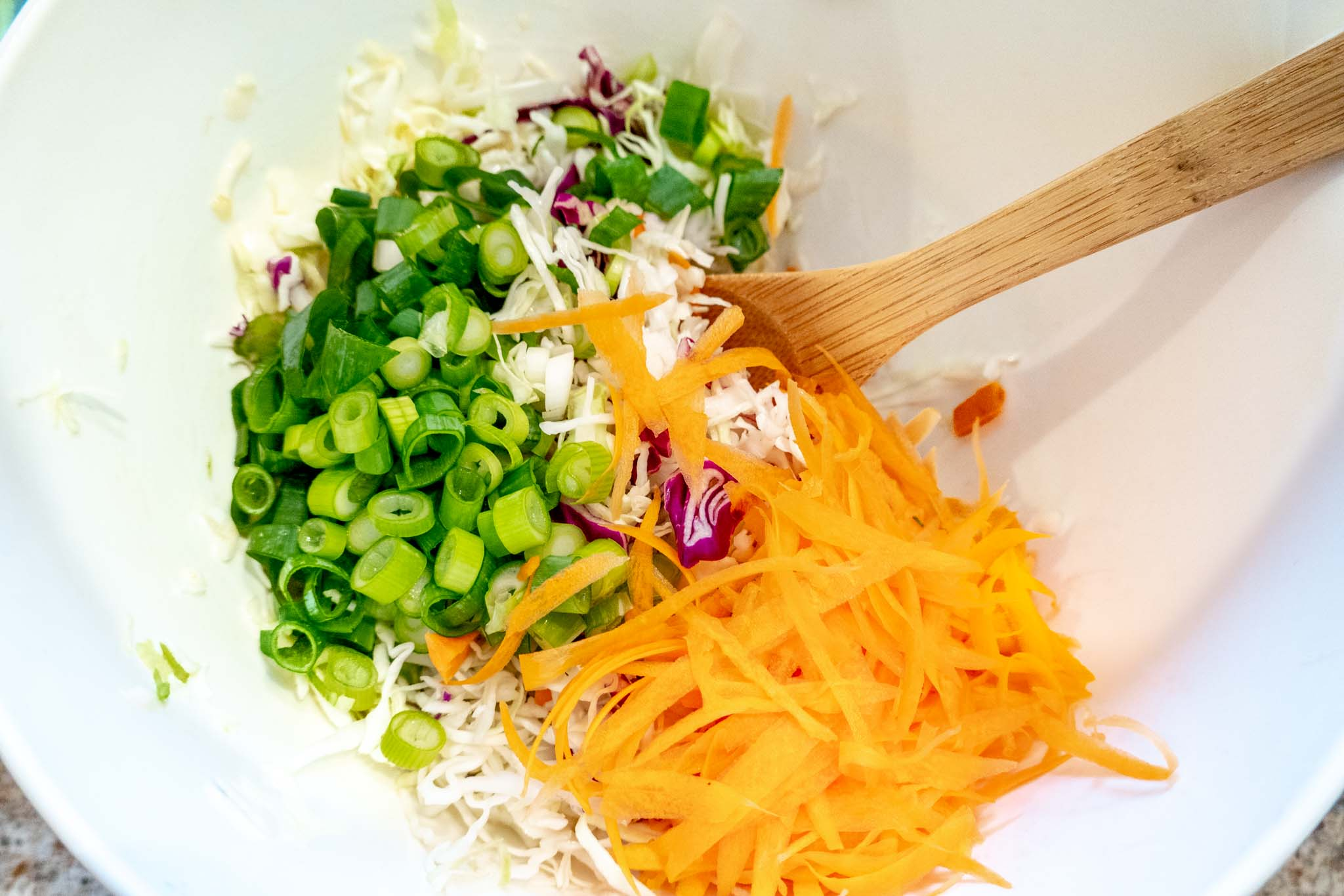 Chopped cabbage, carrots, and scallions in a bowl
