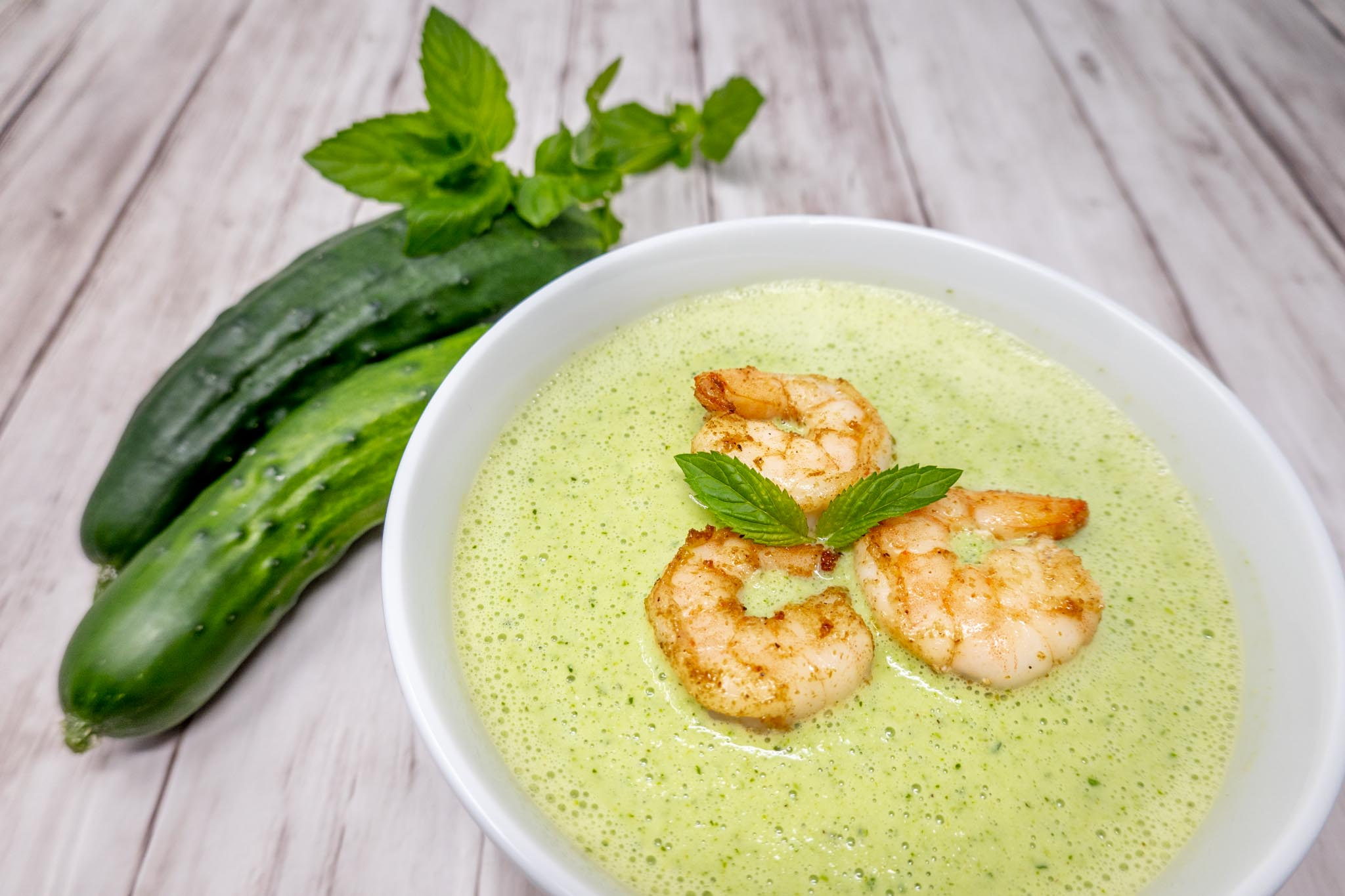 Bowl of green gazpacho topped with shrimp next to cucumbers and herbs