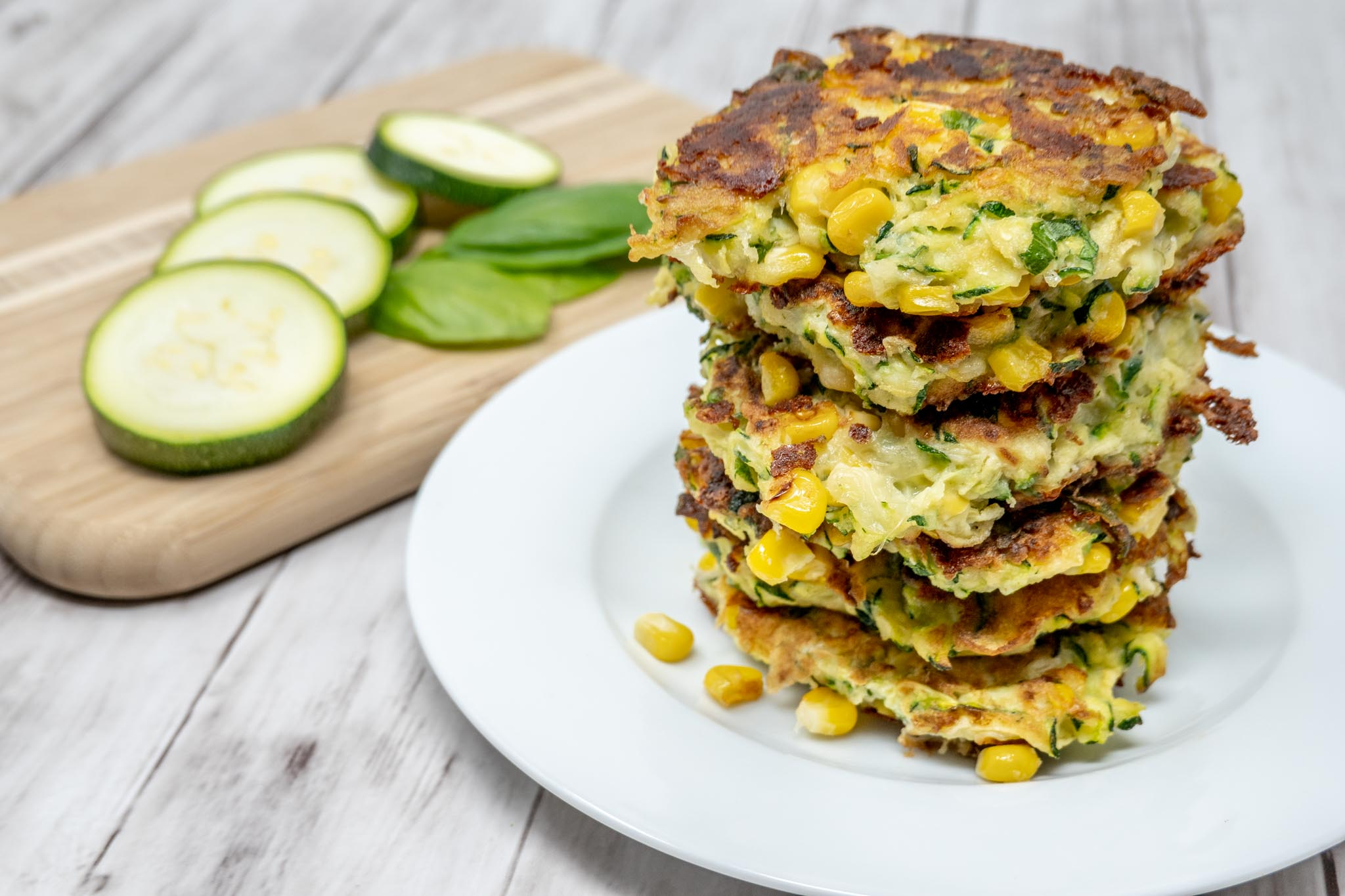 Stack of corn and zucchini fritters on a plate beside slices of zucchini