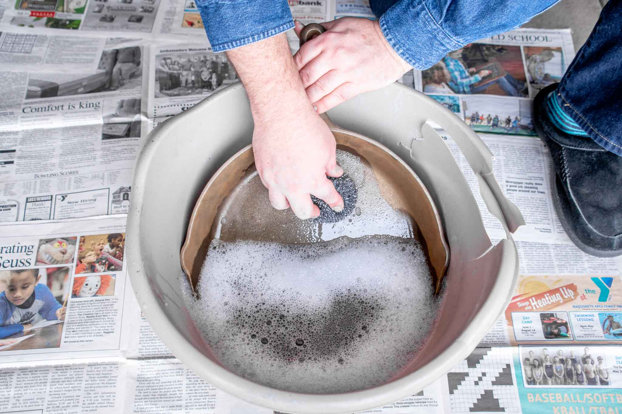 A pan being washed with steel wool