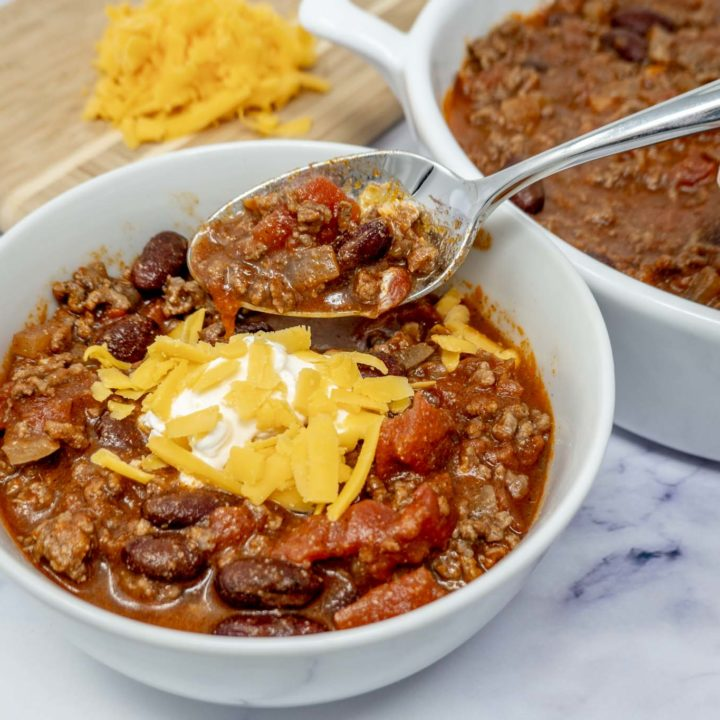 Spoon in a bowl of chili topped with cheese and sour cream