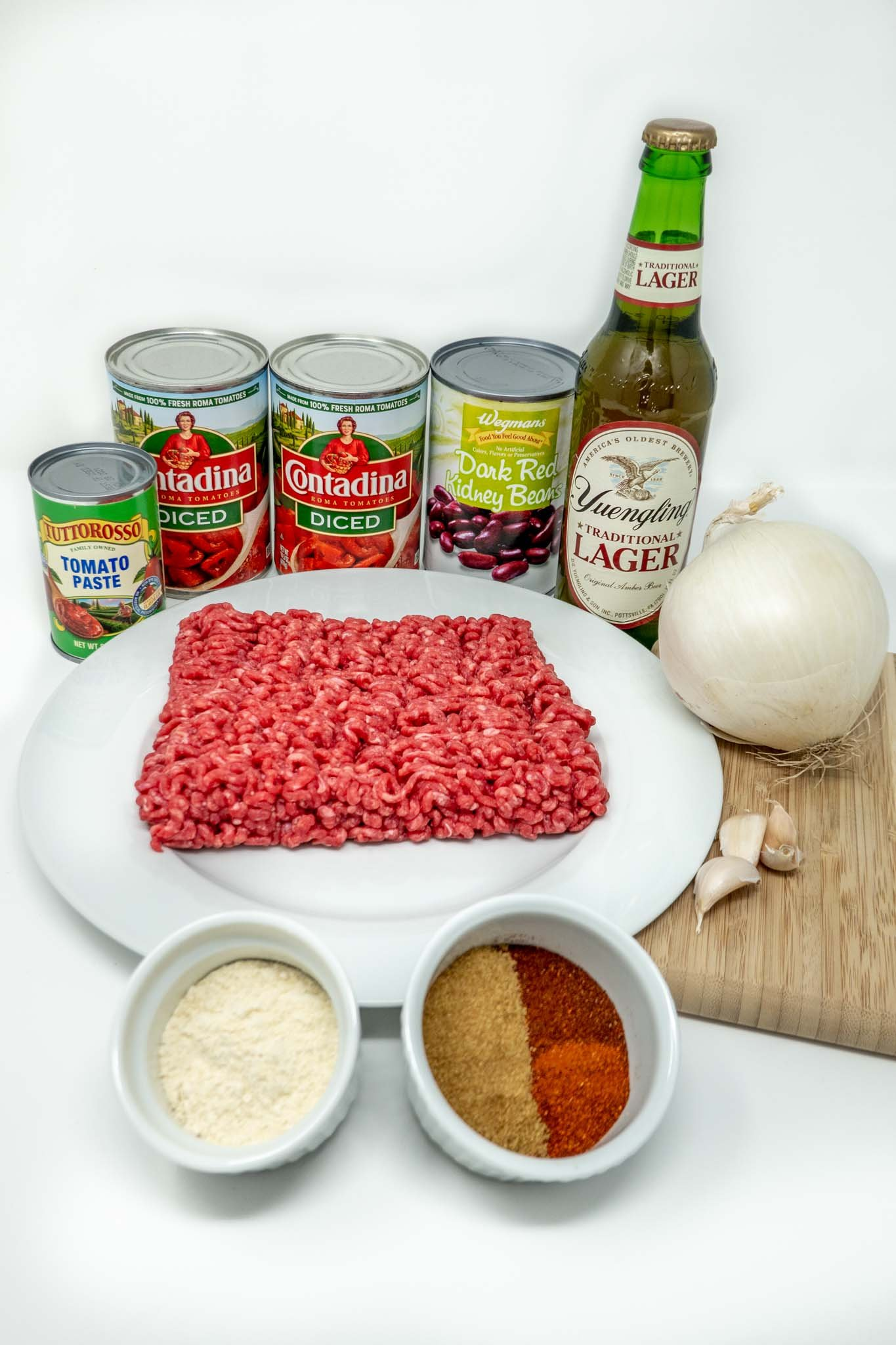 Beef, onion, garlic cloves, spices, masa harina, beer bottle, and cans of tomatoes, beans, and tomato paste