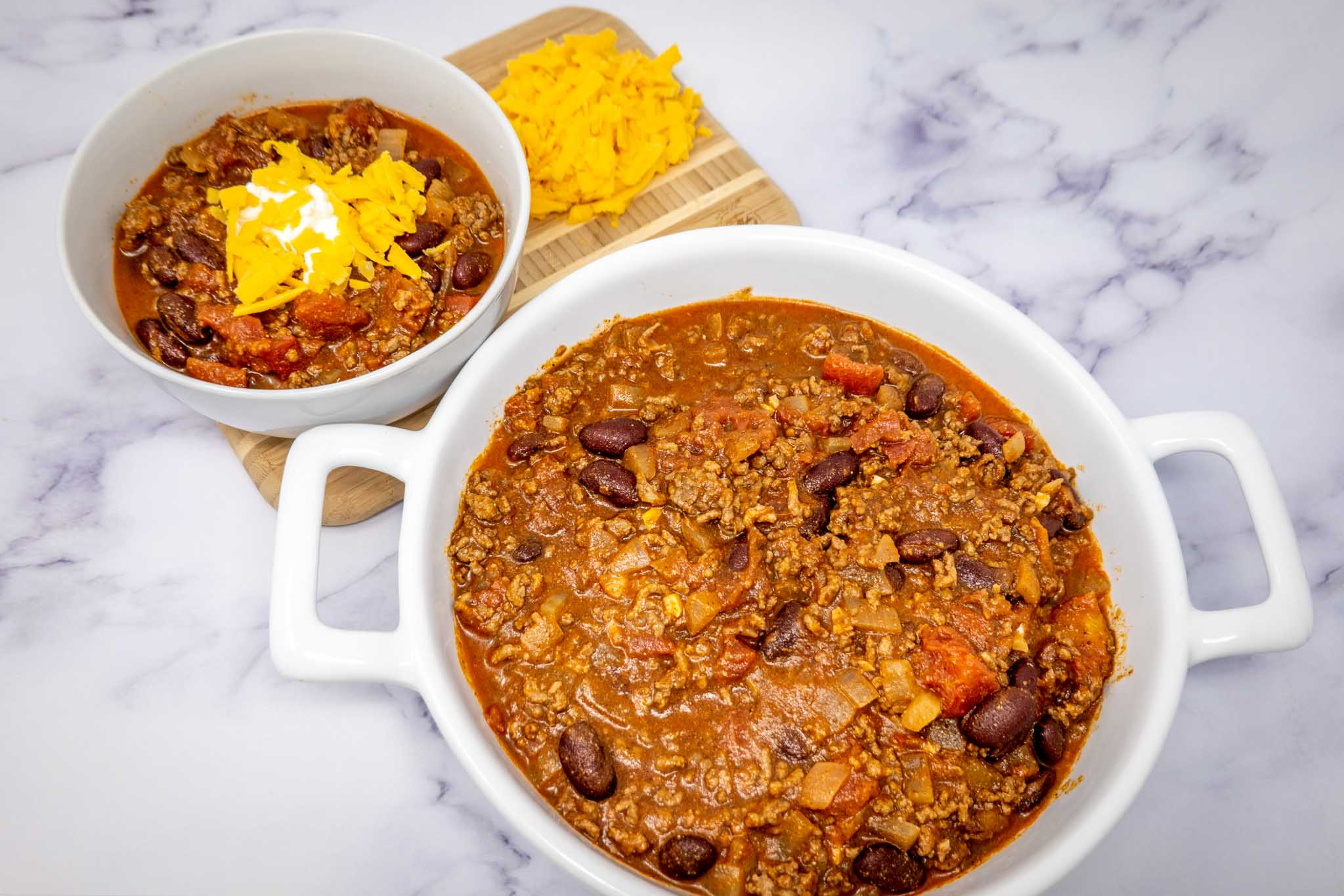 Dish and bowl of chili with shredded cheddar cheese