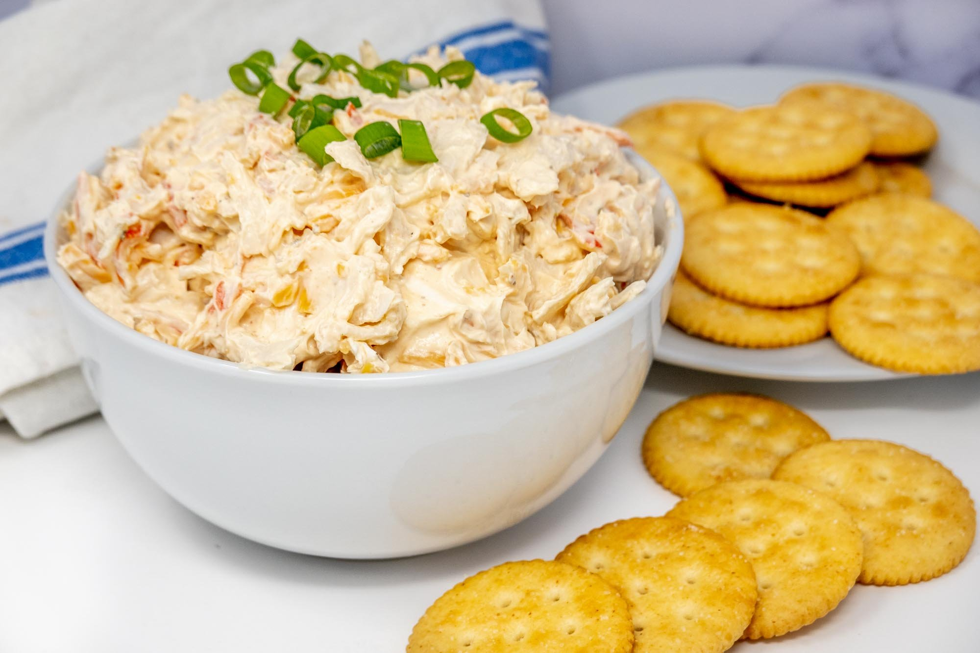 Bowl of crab dip topped with scallions beside a pile of Ritz crackers