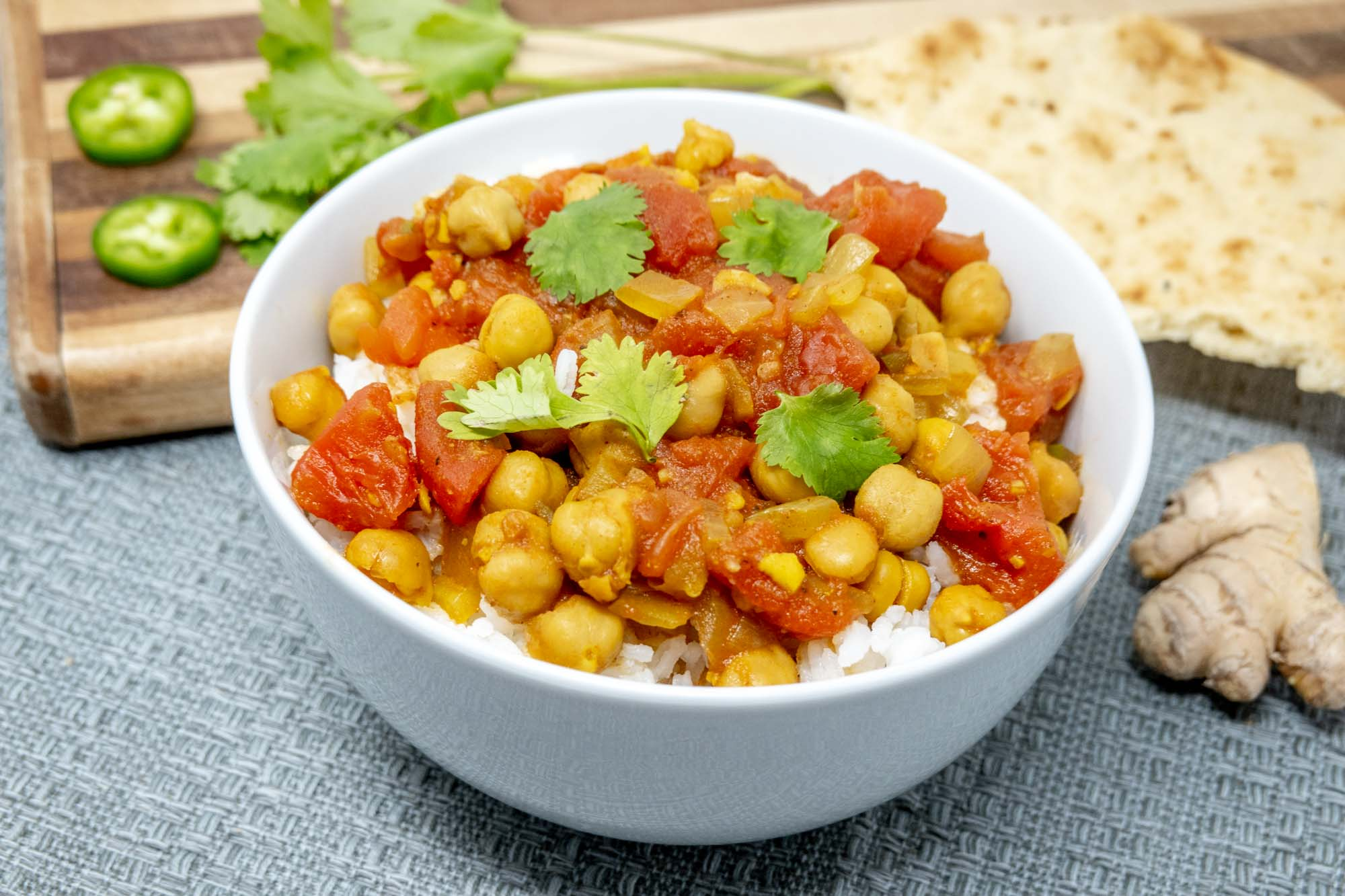 Bowl of rice topped with chickpea and tomato mixture beside ginger and jalapeno slices