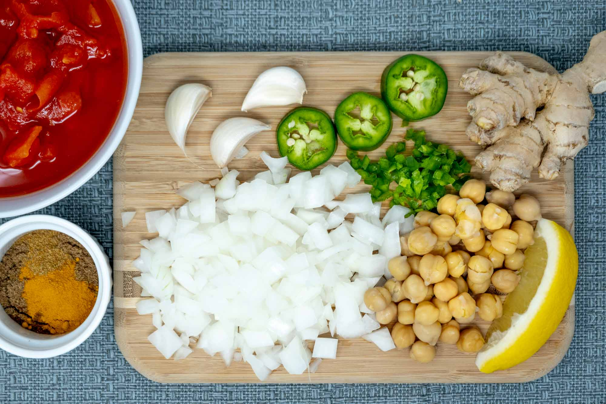 Ginger, garlic cloves, jalapeno, chickpeas, lemon, and diced onion on a cutting board beside bowls of spices and diced tomatoes