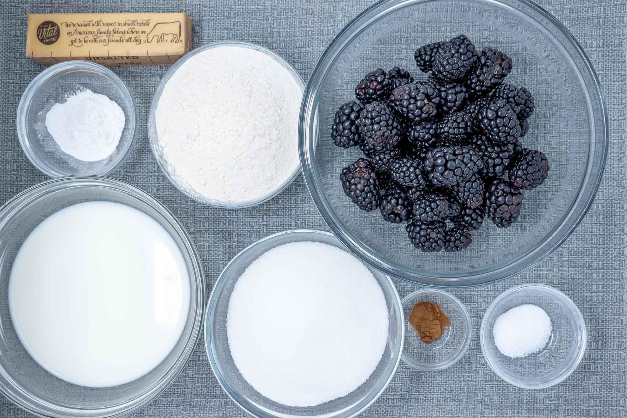 Blackberries, cinnamon, sugar, stick of butter, and other ingredients in bowls on a table