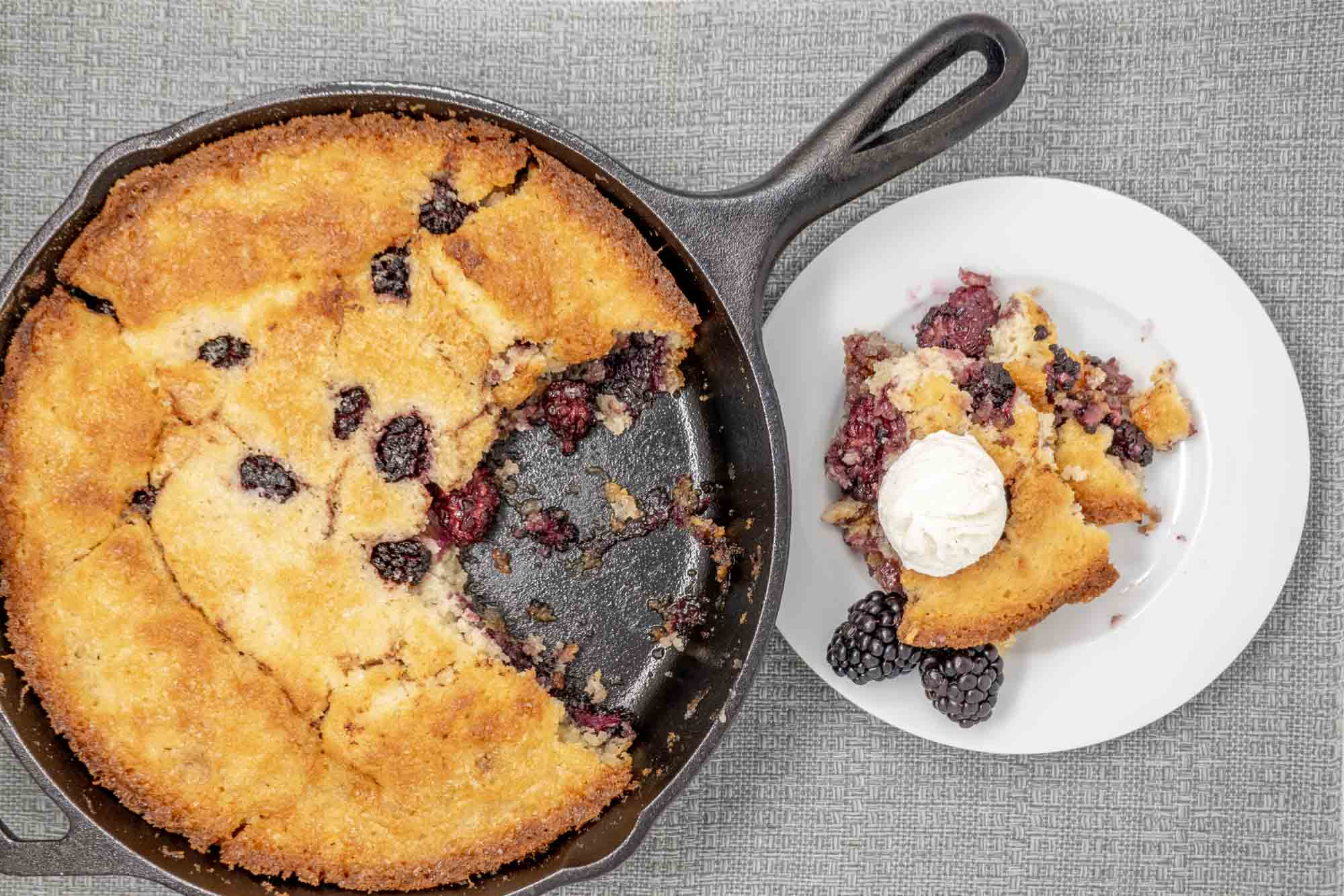 Portion of blackberry cobbler topped with ice cream on a plate next to the rest of the cobbler in a cast iron skillet