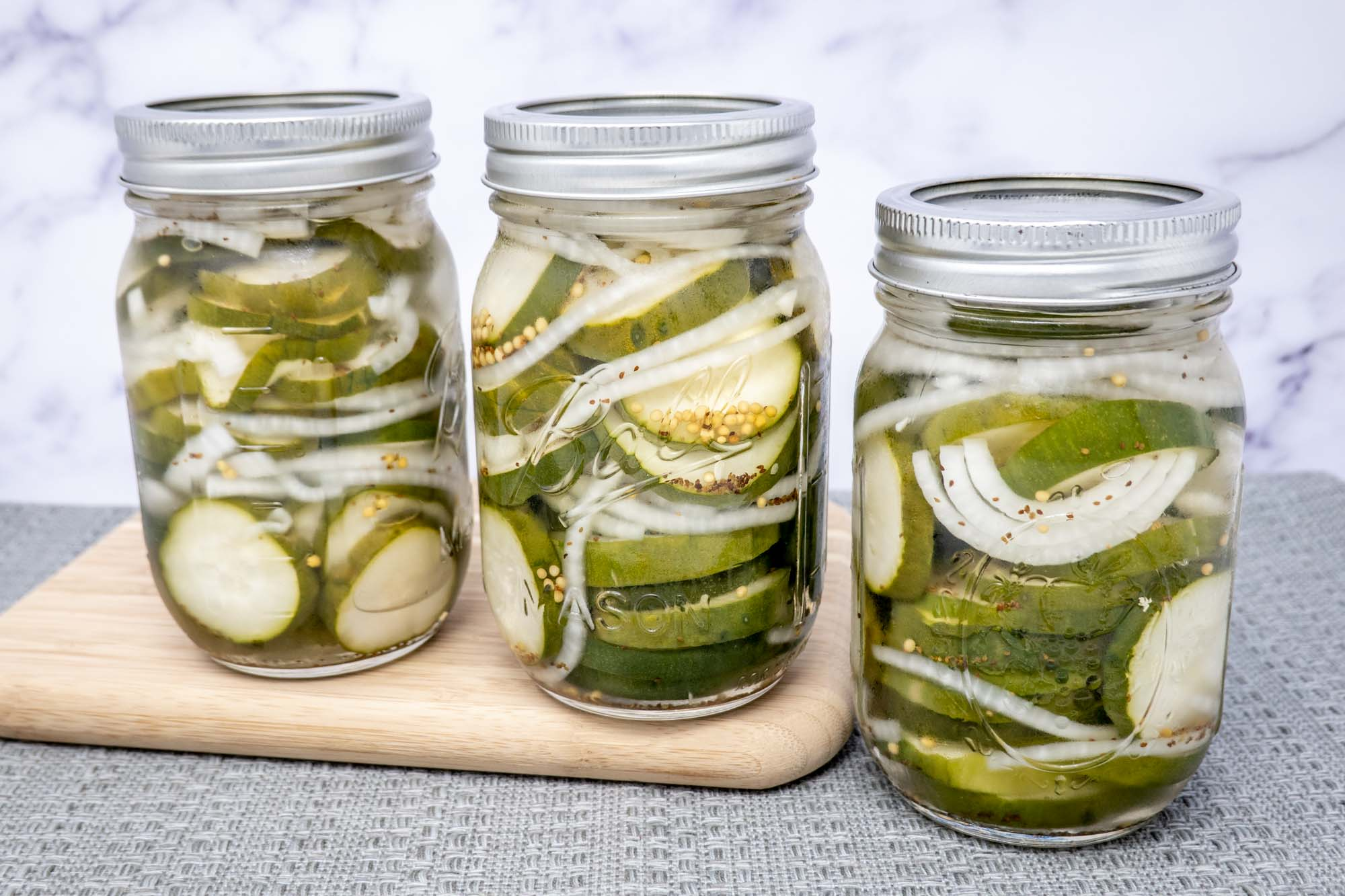 Three jars of pickled cucumbers and onions two of which are sitting on a cutting board